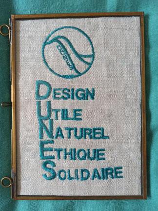 Cadre avec logo D.U.N.E.S. Design Utile Naturel Ethique Solidaire brodé couleur turquoise