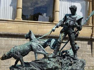 une statue represente un guerrier tenant en laisse 2 chiens par coach canin 16 educateur canin à cognac