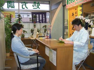 テクノ高木薬局店内の写真:カウンター越しにお客さまと向かい合い、ご相談をお伺いしてる様子。