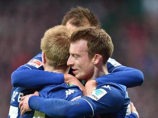Die Wolfsburger herzen ihren Torschützen vom Dienst Bas Dost (hinten). Foto: Carmen Jaspersen
