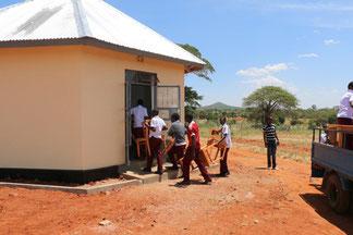 Sieben Jungen und Mädchen tragen Stühle in einen neuen Gebäudeteil der One World Secondary School Kilimanjaro.