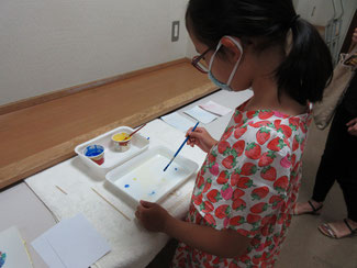 ①筆にアクリル絵の具をつけ、水面に触れるようにして絵の具を3か所程度落としていきます