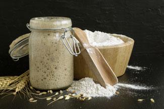 Sauerteig im Glas und Holzschüssel mit Mehl und Schaufel