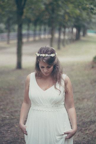 Eine Braut läuft im Park des Schloss Philippruhe Hanau und blickt auf den Boden.