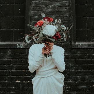 Eine Braut hält ihren Brautstrauß vor ihr Gesicht.