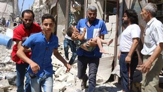 Nach einem Luftschlag in dem von Rebellen gehaltenen Viertel Al-Qatirji in Aleppo tragen Helfer ein Kind aus den Trümmern. © THAER MOHAMMED/AFP/Getty Images