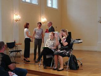 Das Foto zeigt Herrn Zenker am Rednerpult. Daneben stehen Frau Schachler und Frau Kübler. Vor dem Rednerpult sitzen 2 Gebärdensrach-Dolmetscherinnnen.