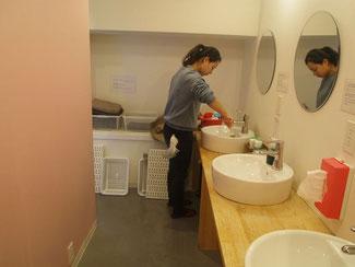 シャワールーム前の洗面台を掃除するスタッフ