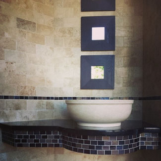 Cream natural stone vessel sink atop a Black Galaxy granite countertop with bronze and black glass mosaic accent.