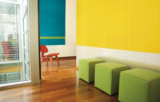 Room with wood floors and walls with yellow, white, blue, and lime green ceramic tiles. Three lime green cube-shaped seats line the yellow wall.