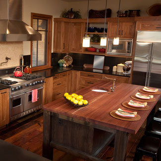Rustic style kitchen with medium brown wood cabinets, bronze door pulls, black quartz countertops, and a butcher block island top.
