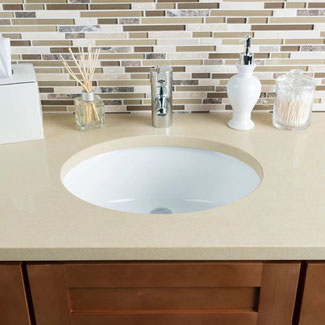 Bathroom vanity with light sand-colored quartz countertop, white oval undermount sink, cinnamon wood cabinets, and beige and brown glass and stone backsplash mosaic.
