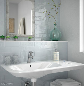 Bathroom with pale blue-gray ceramic tile and white sink. A silver-framed mirror hangs on the wall behind the sink.