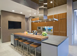 Soapstone island with a large piece of butcher block on it  in the middle of a modern kitchen.