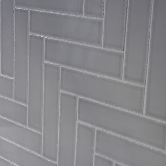 A close up of a gray tile with jagged edges set in a herringbone pattern.