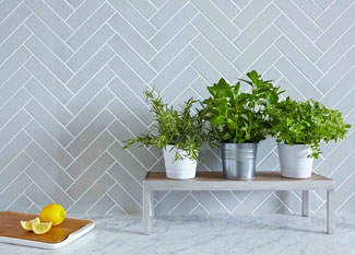 White marble countertop with a light blue herringbone ceramic tile backsplash, sliced lemons and potted plants.