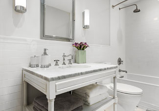 All-white bathroom with a marble vanity top, toilet, and shower/tub combo.