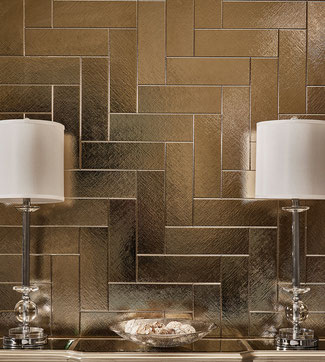 Textured gold brick tiles in a herringbone pattern behind a credenza with two lamps.