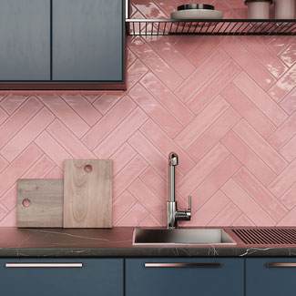 Pink gloss kitchen backsplash tile with dark blue-grey cabinets, a black marble countertop, stainless steel sink, and wood cutting boards.