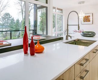 White quartz countertops in a modern kitchen with bright red and orange vases on the countertop.