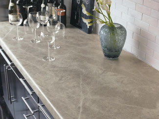 Veined sandy-colored Formica countertops with wine glasses and a flower vase.