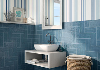 Corner of a bathroom with blue ceramic subway tile set in a herringbone pattern behind a floating vanity with a white vessel sink.
