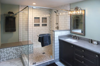 A bathroom with a dark vanity, white subway tile shower with a pebble tile shower pan.