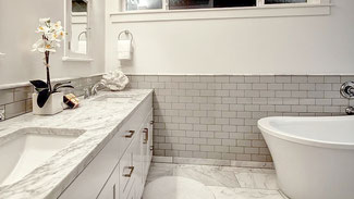 Bathroom with marble countertop and floor tile, gray subway tile wainscoting, white painted walls, and white soaking tub.
