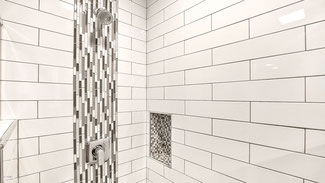 Inside a shower. Walls are covered in long white subway tiles in an offset brick pattern. There is a recessed shelf covered in a white and gray square mosaic. There is a vertical stripe of a matching linear mosaic behind the shower head.