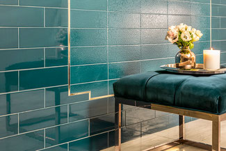 Teal wall tiles with gold trim behind a teal ottoman with flowers and a candle sitting on a tray.