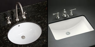 A white oval and white rectangle undermount sinks in black countertops.