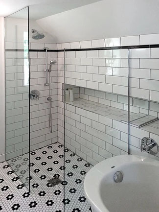 Shower with white subway tiles and black and white hexagon floor tiles