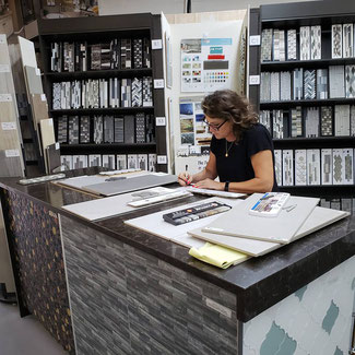 Tile Lines designer Heidi working at a table in the Tile Lines showroom, surrounded by tile samples.