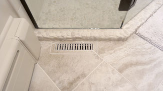 Bathroom floor with a tiled heat register in white tile.