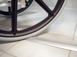Close up of a wheelchair wheel rolling over the rubber collapsible lip of the ShowerProfile-WS