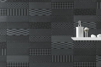 Black tile with multiple patterns on a wall. There is a white shelf with a shaving kit on it hanging on the wall.