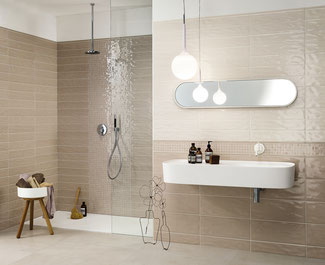 Bathroom with walk-in curbless shower. The walls are tiled with light tan- and biscuit-colored tiles. There's a long white wall-mounted sink below a long oval mirror.