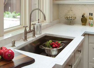 Cambria Ella kitchen countertop with stainless steel undermount sink and a colander filled with fresh radishes.