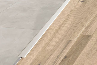 Schluter Reno T in satin aluminum bridges the edges of a wood and gray tile floor