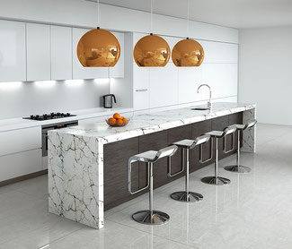 A white marble countertop with brown veins on a dark wood island. the side cabinets are white with white countertops. There are large orange copper pendant lights above the island.