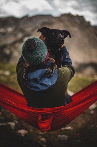 Eine Frau sitzt mit Hund in einer Hängematte vor Bergkulisse. Photo by Patrick Hendry on Unsplash