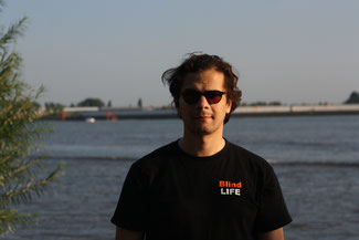 Erdin spaziert an in der Hafencity. Schwarz gekleidet mit Blinden steht. Entfernt sich von der Kamera. Links sind im Hintergrund diverse Objekte zu sehen. Rechts ein Geländer und dahinter das Elbwasser.