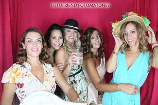 Chicas posando divertidas en fotomatón de cortinas rojas