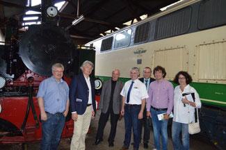 Verbandsbürgermeister Johannes Bell und Geschäftsführer Stefan Raab zeigen den FDP-Vertretern im Lokschuppen der Brohltalbahn die historische Dampflokomotive.