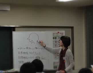 ホワイトボードに図説する講師