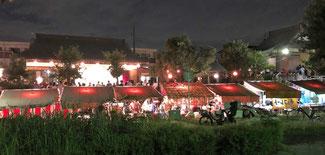 天神公園から見た演芸会の様子 左側に社務所のステージ 右側が神社 手前に屋台が並ぶ
