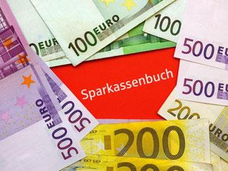 Klassische Spareinlage: Ein Sparbuch der Sparkasse liegt unter Euro-Geldscheinen. Foto: Patrick Pleul