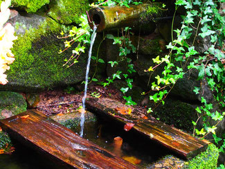 mit Moos überdeckt der alte Granit-Stein-Brunnen