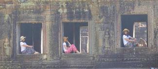Bild: Drei Frauen ruhen sich in den Fenstern eines Tempels in Angkor Watt aus.