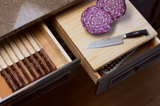 Open kitchen cabinet drawers with knives, cutting boards, and cut red cabbage.